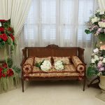 Red couch sittee with flowers