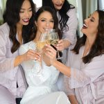 Bride celebrates with bridesmaids with champagne